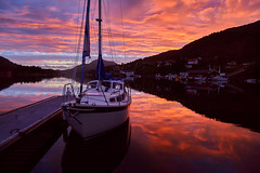 Beautiful sunset at the Norwegian fjord,  yachts in port with hills on the background. (Sergey_pro) Tags: sea sunsetharbour ocean orange red port cloud sky sunset twilight water yellow dusk summer sun beautiful harbor tourism outdoor yacht landscape bay boat pier seascape ship travel europe norway norwegian fjord scandinavia cloudscape relaxation beauty city coast evening glowing marine mountain hill quiet