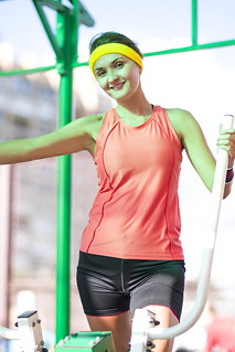 Fitness Ideas and Concepts. Smiling Caucasian Female Athlete in Professional Outfit Having Stepping Exercises for Legs and Arms Muscles.Posing Relaxed.