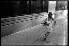 HarperRunningDowntownF2sb50Ilford6400_img006 (Johnny Martyr) Tags: lines running girl charging charge converge convergence vanishingpoint run go nikon ilford kodak 6400isodaylight 3200isodaytime grain grainy contrast asphalt concrete line math composition moment abstractportrait portrait documentary photojouralism style littlegirlrunning nostalgia thepast goingaway going fast