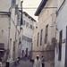 Narrow Zanzibar street, old man (seated) chanting.