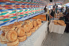 The Breadmaker (peterkelly) Tags: uzbekistan tashkent chorsubazaar asia digital canon 6d gadventures centralasiaadventurealmatytotashkent bread table market bazaar seller vendor hat