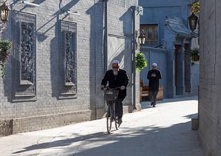 Hui muslim man riding a bicycle in the street, Gansu province, Linxia, China
