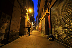 Welcome to the night (Daniel Nebreda Lucea) Tags: noche street city ciudad color old vieja antigua urbana urban alley callejon dark oscuro atmosphere atmosfera people gente man hombre textures texturas lights luces light luz shadows sombras fear miedo darkness oscuridad zaragoza canon 60d 1018mm architecture arquitetura houses casas building edificio construccion silhouette silueta travel viajar shops tiendas perspective perspectiva composition composicion lines shapes formas lineas aragon españa spain europe europa long exposure larga exposicion floor suelo blue sly cielo azul golden house hora