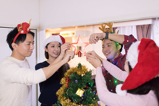 Young friends setting up star ornament on Christmas tree