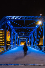 On the Blue Bridge at Night in Grand Rapids (Lee Rentz) Tags: 1892 575long bluebridge gvsu grandrapids grandrapidsriverwalk grandrapidsandindianarailroad grandvalleystateuniversity kentcounty lit november prattthroughtruss alone america autumn blue bridge city converted cool danger dangerous darkness dogs downtown eerie ethereal evening fall grandriver group historic historical illuminated lighted lighting litup magical metal michigan midwest midwestern mysterious night northamerica panel path pedestrian pinconnected railroad railway river route sidewalk span steel stream trail transcendental truss urban usa vertical walking woman
