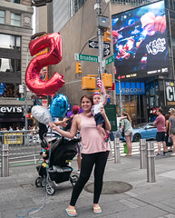5 Months? (UrbanphotoZ) Tags: mother son baby 4thofjuly americanflag balloons stroller flaghat flag hat red white blue 5 triumphant broadway w44st viacom wildnout billboard levis plaza smiling pedestrians timessquare westside midtown manhattan newyorkcity newyork nyc ny