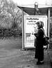 Searching (A. Yousuf Kurniawan) Tags: woman blackandwhite monochrome islam muslim streetphotography urbanlife busstop cameraphone decisivemoment activity sign
