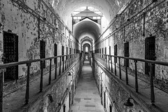 Symmetrical Cells (RaulCano82) Tags: cell prison prisoncell cellblock blackandwhite 80d canon raulcano philly philadelphia pa easternstatepenitentiary easternstate penitentiary jail photography inmate decay grit filth rotting old historic peeling rusty iron steel bars ironbars symmetry hall hallway corridor haunted