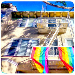 ( All the colors in the crayon box ) (Wandering Dom) Tags: looking up california architecture building flags rainbow colors humans people time life reality dreams being nothingness balcony ladders windows fire escape earth multiverse roam wandering urban street living
