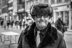 Meanwhile... (Leanne Boulton) Tags: portrait urban street candid portraiture streetphotography candidstreetphotography candidportrait streetportrait eyecontact candideyecontact streetlife man male face facial expression eyes look emotion feeling mood winter cold fur furry hat coat 70s style fashion tone texture detail depthoffield bokeh naturallight outdoor light shade shadow city scene human life living humanity society culture canon canon5d 5dmkiii 70mm chracter ef2470mmf28liiusm black white blackwhite bw mono blackandwhite monochrome glasgow scotland uk