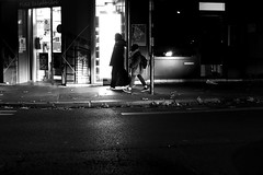 In front of the lit shop window (pascalcolin1) Tags: paris13 femme woman enfant child nuit night lumière light shop magasin photoderue streetview urbanarte noiretblanc blackandwhite photopascalcolin canon50mm canon 50mm