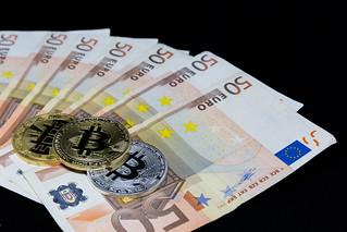 Geldscheine und Bitcoin-Münzen