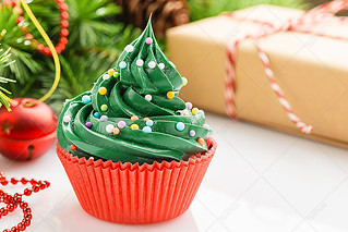 Christmas green cupcake in red cup with decorations