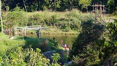 Cleaning up (LeftCoastKenny) Tags: madagascar ranomafana hotelthermalranomafana trees grass brush river ropebridge people bathing day7