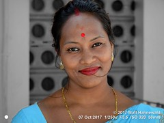2017-09a India's Northeast (22a) (Matt Hahnewald) Tags: matthahnewaldphotography facingtheworld head face forehead bindi makeup sindoor eyes lips lipstick consent emotion cultural hinduism puja temple devotee beauty mahabhairav tezpur assam asian indian assamese female adult mature woman picture photo background primelens horizontal street portrait closeup outdoor color editing posing authentic smiling beautiful attractive charming blackandwhite greyscale monochrome nikond3100 photoshop travel 50mm cluttered oneperson northeast postprocessing expression headshot almondshapedeyes earring nikkorafs50mmf18g lookingcamera fullfaceview 4x3ratio 1200x900pixels resized