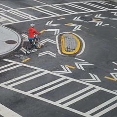 island in the stream (jim_ATL) Tags: traffic island pavement marker street yellow circle bicycle bike rider cyclist orange jacket atlanta