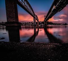 The bridges at magic hour (NikNak Allen) Tags: plymouth devon saltash cornwall sand water river tamar rivertamarroad bridgetrain bridgerail bridgebrunel bridgebrunelcrossingrailwayroadshadowsreflectionreflectionssunskycloudcloudssunrisemorningearlylowlong exposure sky bridge bridges