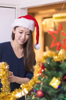 Young woman setting up Christmas tree in house