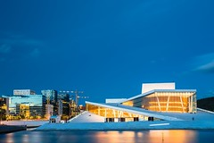 Oslo Norway. Evening View Of Illuminated Opera Ballet House Among High-Rise Buildings Under Blue Sky (altextravel) Tags: ballet nationalopera architecture art attraction blue building city culture destination europe evening famous glow house illuminated illumination landmark light national night norway norwegian opera operahouse oslo outdoor place scandinavia sightseeing sky street summer theater theatre tourism town travel twilight urban vacation visit white yellow no