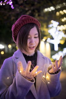 Young woman playing with light cable in Christmas night