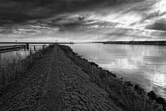 White Light, Black Dike (Alfred Grupstra) Tags: blackandwhite sea nature water landscape sky outdoors coastline pier cloudsky beach bridgemanmadestructure scenics nopeople river architecture cloudscape watersedge jetty