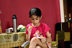 Little girl reading over cookies (vireshwali) Tags: little girl reading book evening indoors interior home relaxed relax d5600 nikon gimp india life