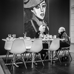 Mme. Schokko Is Displeased... (tim.perdue) Tags: mme schokko madame columbus museum art cma cmoa mycma cafe restaurant two women ladies people figures street candid table wendys carryout painting look stare red hat alexej jawlensky cameron mitchell chairs displeased fast food monovember 2017 monovember2017 olympus omd em10mkii panasonic lumix 1232mm
