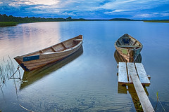Travel Destinations Concepts. Peaceful Picturesque Landscape of The Strusto Lake with Wooden Boat at Foreground. Lake is a Part of National Braslav Lakes Reserve. (DmitryMorgan) Tags: belarus braslau braslav landscape strusto strustolake belarussian boat bound calm clouds cloudy country countryside distinctive dusk evening floating glassy historic honor idyllic island islands journey lake lakecountry lakes light mirrorlikesurface national natural nobody outdoor path proud rope rural scene scenery shore signature site sky summer traveldestination vacation voyage wooden