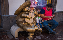 2017 - Mexico - Tlaquepaque - Rodo Padilla Bronze (Ted's photos - For Me & You) Tags: 2017 cropped guadalajara mexico nikon nikond750 nikonfx tedmcgrath tedsphotos tedsphotosmexico vignetting guadalajaramexico guadalajarajalisco rodopadilla tlaquepaquemexico rodopadillatlaquepaque tlaquepaquerodopadilla bronze bronzesculpture sculpture tlaquepaquejaliscomexico seating seated sitting musician guitar artist entertainer uke kid child father tethered sombrero denim jeans bench