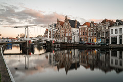 Crossing the River (McQuaide Photography) Tags: haarlem noordholland northholland netherlands nederland holland dutch europe sony a7rii ilce7rm2 alpha mirrorless 1635mm sonyzeiss zeiss variotessar fullframe mcquaidephotography adobe photoshop lightroom tripod manfrotto light licht availablelight sunset zonsongergang water reflection longexposure stad city urban river spaarne rivier waterside lowlight outdoor outside waterfront architecture skyline building gebouw wideangle wideanglelens groothoek calm peaceful tranquil landmark bridge drawbridge ophaalbrug autumn nd neutraldensity ndfilter bwfilters rijksmonument deolyphant gravestenenbrug