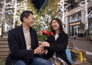 Happy young wife receiving flower from husband