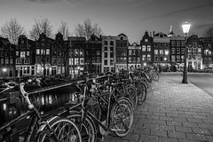 Amsterdam Parking (McQuaide Photography) Tags: amsterdam noordholland northholland netherlands nederland holland dutch europe sony a7rii ilce7rm2 alpha mirrorless 1635mm sonyzeiss zeiss variotessar fullframe mcquaidephotography lightroom adobe photoshop tripod manfrotto stad city urban waterside lowlight architecture outdoor outside building longexposure capitalcity houses house huizen huis bike bicycle fiets parked parking bridge krommewaal blackandwhite blackwhite bw mono monochrome classic authentic night nightphotography streetlight street straat