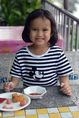 mickey mouse girl smiling between bites (the foreign photographer - ฝรั่งถ่) Tags: girl child seated table bite sized meat khlong lat phrao portraits bangkhen bangkok thailand nikon d3200
