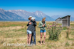 A man hugs a woman lovely while a girl plays a recorder in Jackson Hole, Grand Tetons National Park, Teton County, Wyoming (Remsberg Photos) Tags: eclipse grandteton jackson landscape mountains nationalpark solar tetons west wyoming colorimage grandtetonnationalpark tetonrange mountainrange rockymountains mountain nature westernusa jacksonhole tourism horizontal outdoors skyline sky traveldesintations clearskies vast boundless broad expanse openspace loving togetherness affection love hugging recorder happiness tender family usa