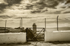 City Depression (panos_adgr) Tags: nikon d7200 city factory fence net keratsini charavgi greece places from past sky clouds door drama mood depression street view cityscape nikkor afs 1855 vr