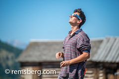 Young adult male uses special glasses to view solar eclipse, Grand Tetons National Park, Teton County, Wyoming (Remsberg Photos) Tags: eclipse grandteton jackson landscape mountains nationalpark solar tetons west wyoming colorimage grandtetonnationalpark westernusa jacksonhole tourism horizontal outdoors traveldesintations clearskies solareclipse lookingthroughanobject concentration curiosity day watching glasses solareclipseglasses youngadult youngmale onlymen usa