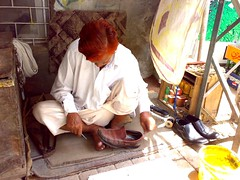 The shoe doctor! (farrukhathar) Tags: cobler cobbler shoes hush puppies red sunlight innocence old man 2009 repair lahore pakistan handy work hard afternoon street side shade poor self employed flickr memories thread needle stitch past nokia n73 explore inexplore