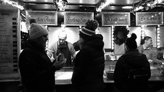 festive market at night 014 (byronv2) Tags: festive festivemarket christmasmarket peoplewatching candid street princesstreet princesstreetgardens edinburgh edimbourg edinburghbynight night nuit nacht blackandwhite blackwhite bw monochrome market mound food cafe foodstall burgers sausages hotdogs cooking eating dining diner