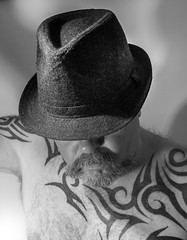 Trilby hat man. (CWhatPhotos) Tags: black white mono monochrome smile smiles cwhatphotos tattoo tattooed tattoos tatts tat tribal ink inked eyes moody mad torso upper body goatee photographs photograph pics pictures pic picture image images foto fotos photography that have which with contain mk digital camera lens micro four thirds em5 ii me man male self portrait selfee selfie mine face dark shadow light studio lights shadows trilby hat head wear nobody beard hairy chin
