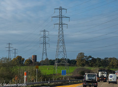 Four Pylons & A Tower (M C Smith) Tags: powerlines motorway traffic trucks vans signs tower pentax k3 blue clouds white barriers field grass trees hedges green landscape lines