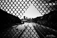 Tear in the Matrix (Hi-Fi Fotos) Tags: pittsburgh 279 highway north chainlink fence hole road freeway city skyline urban noir bw blackandwhite mono nikon d7200 dx hififotos hallewell