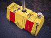 P1090529 (vargandras) Tags: cup coffee street concrete block paint sign yellow red stripe pavement pole rain wet