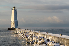 Winter Rising (Aaron Springer) Tags: michigan northernmichigan lakemichigan thegreatlakes frankfortnorthbreakwater frankfortlighthouse sky clouds snow ice lighthouse pier sunrise winter outdoor landscape