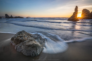 Sunstar through the Sea Stack by the Seashore