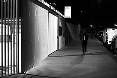 Along the bright barriers (pascalcolin1) Tags: paris13 femme woman nuit night barriere barrier lumière light ombres shadows photoderue streetview urbanarte noiretblanc blackandwhite photopascalcolin canon 50mm canon50mm