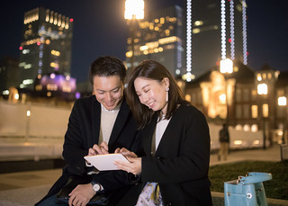 Happy young couple watching screen on digital tablet at night