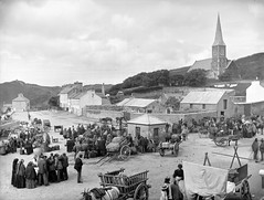 What are they all looking at? (National Library of Ireland on The Commons) Tags: robertfrench williamlawrence lawrencecollection lawrencephotographicstudio thelawrencephotographcollection glassnegative nationallibraryofireland market fair stalls cart creels bales sheets men women church houses clifden countygalway locationidentified