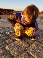 Considering the stone (quinn.anya) Tags: sam preschooler batman superman superhero stone vincent sunset thinking edgartown marthasvineyard