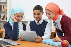 Schoolchildren using tablet at desk in classroom (Unctad_DTL) Tags: apple arab arabic authentic backtoschool background beginner book boy child children class classroom computer culture desk education educational ethnic food girl happy healthy hejab indoor kids laptop learn learning little middleeast middleeastern modern muslim pc people pupil school schoolwork schoolchildren schoolgirl sitting smile student study studying tablet teacher technology using ukraine