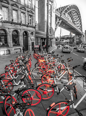 Tyne bridge and some orange bicycles. (CWhatPhotos) Tags: cwhatphotos orange bike bie bicycles hire parked below select selective partial color colour photographs photograph pics pictures pic picture image images foto fotos photography artistic that have which with contain em5 ii omd mkii olympus esystem four thirds digital camera lens olympusomd newcastle city centre center north east england uk red